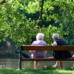 Grandparents enjoying the benefits of being in nature, sitting on a bench in the spring park.
