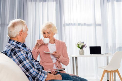 senior couple enjoying cup of coffee in home