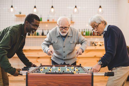three senior men playing foosball