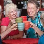 Joyful group of senior adults toasting with coffee mugs.