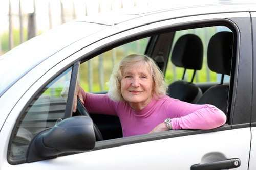 senior woman behind the wheel of a car, smiling out window