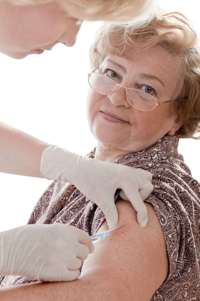 Doctor giving an injection to a senior female