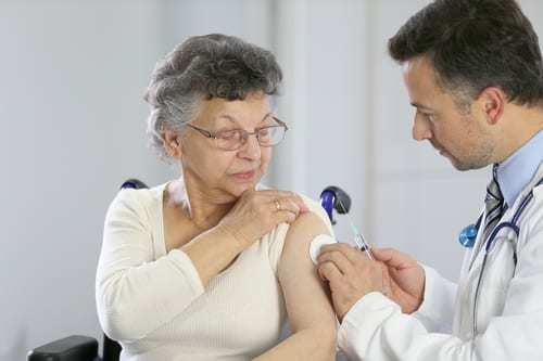 Elderly woman receiving vaccination from doctor