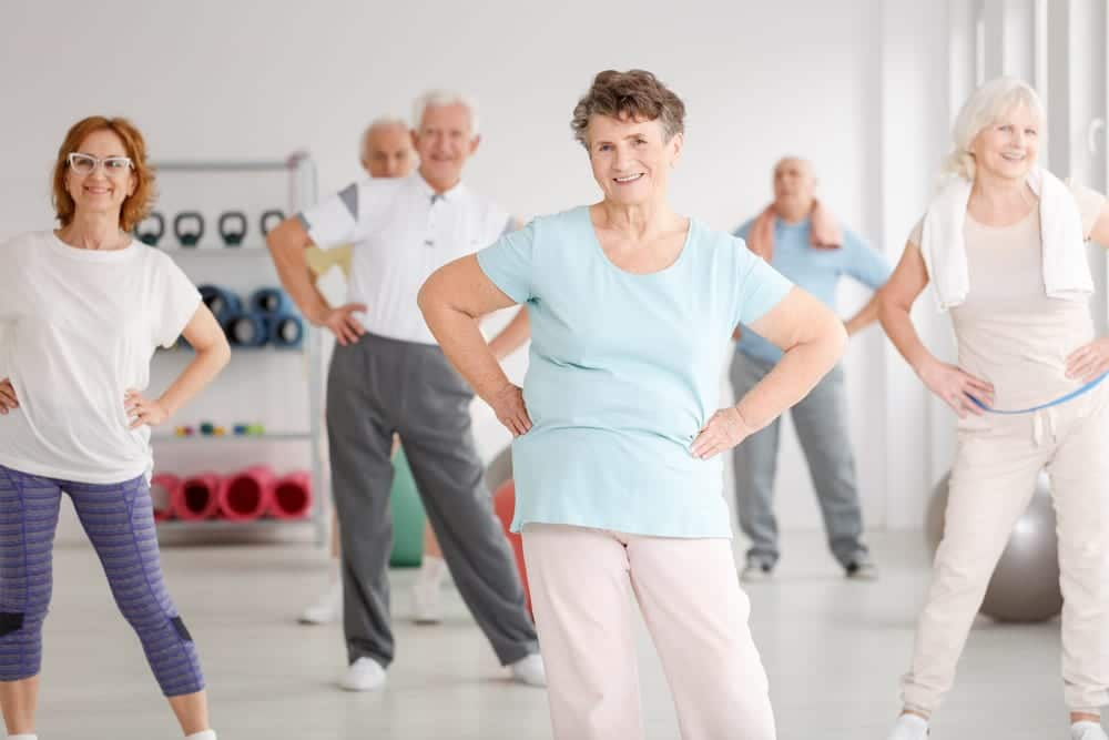 Seniors exercising with hands on hips in workout room