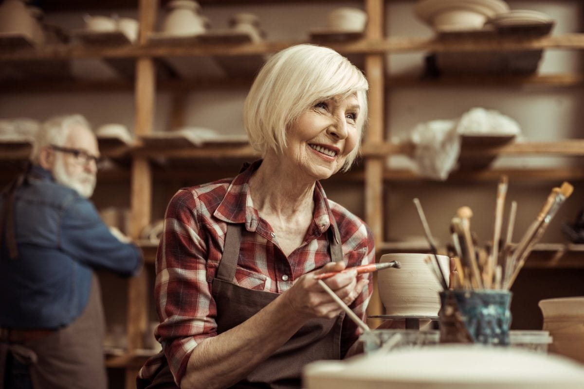 Senior woman painting clay pot at workshop
