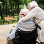senior woman with her arms around senior man in wheelchair