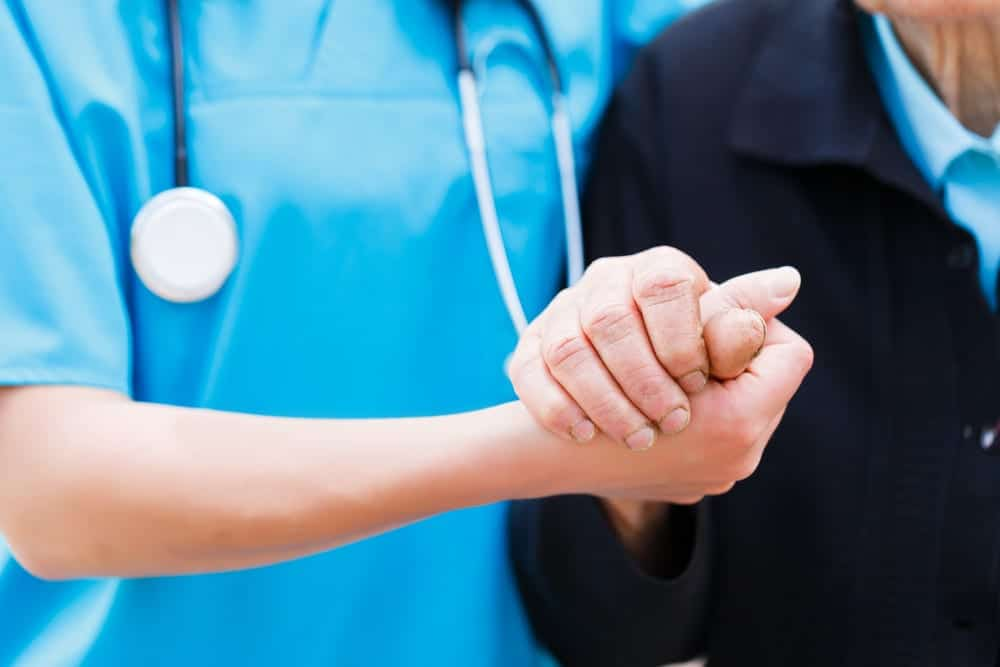 Nurse holding the hand of elderly patient