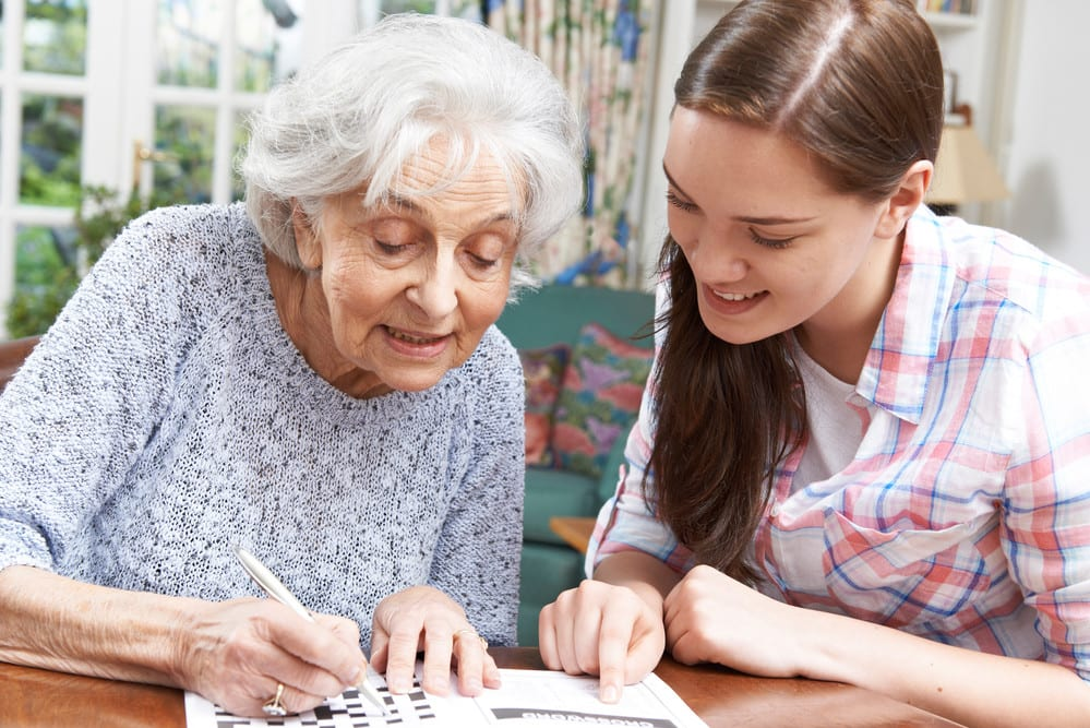 Senior woman and young woman competing crossword puzzle together