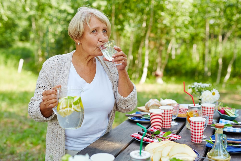Senior woman at picnic table drinking water with lemon