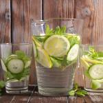 Pitcher of water and two glasses of water with lemon and cucumber slices