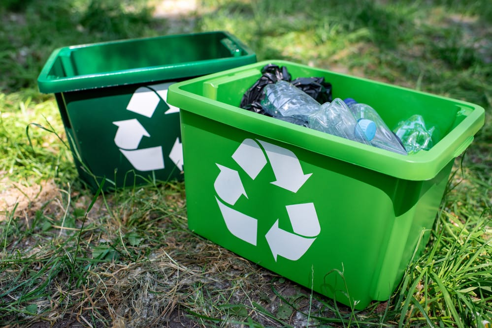 Two recycling containers sitting in the grass, one filled with plastic