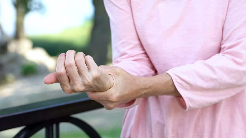 Close-up of senior woman touching wrist with other hand