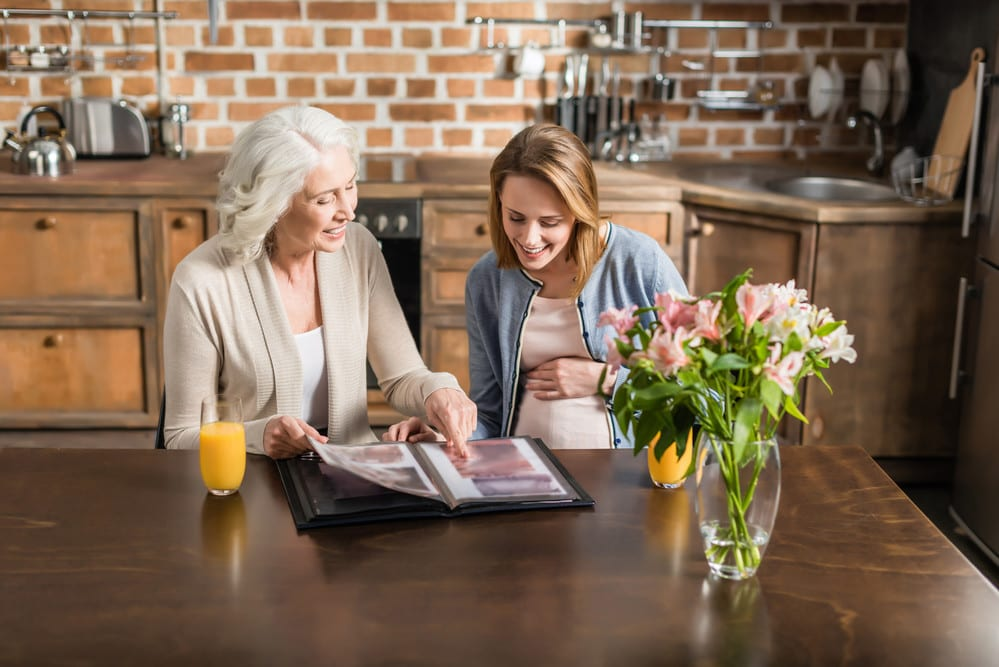 Young pregnant woman looking at photo album with senior woman, both smiling