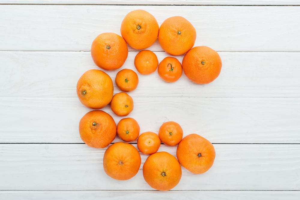 Oranges and tangerines forming the letter C on white wood background