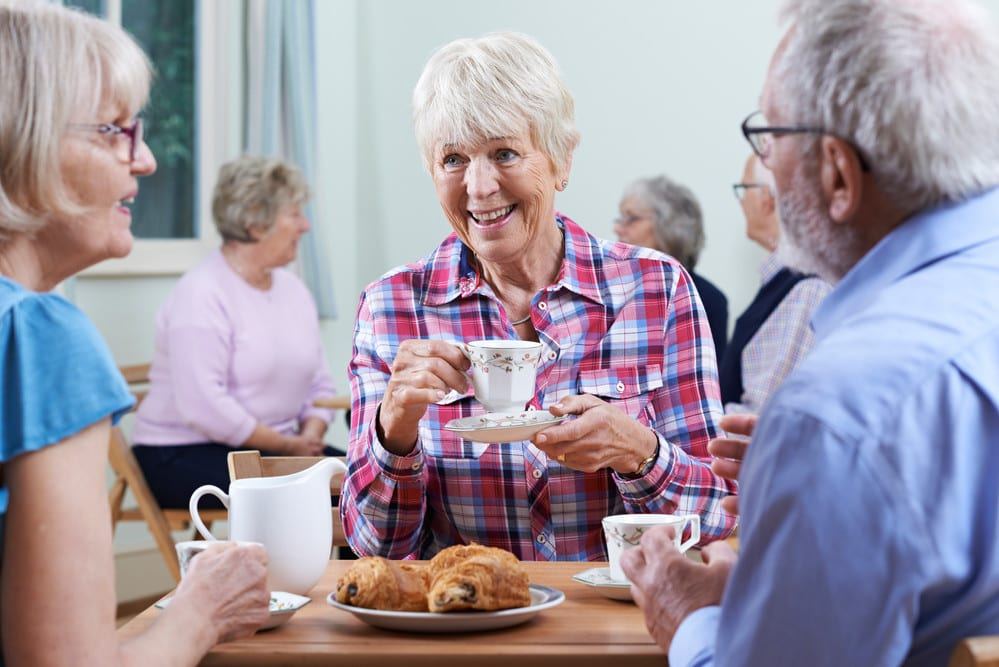 Seniors chatting over tea and pastries