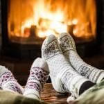 Two pairs of feet (one adult, one child) in fair isle socks in front of the fireplace