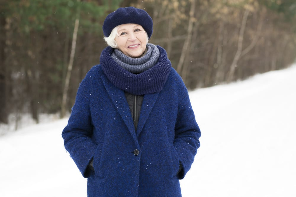 Senior woman smiling, bundled up in coat and scarf, outside in snow