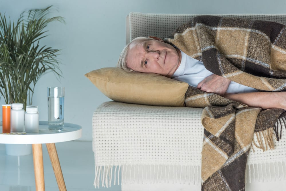 Sick senior man lying on cough under blanket, medications nearby