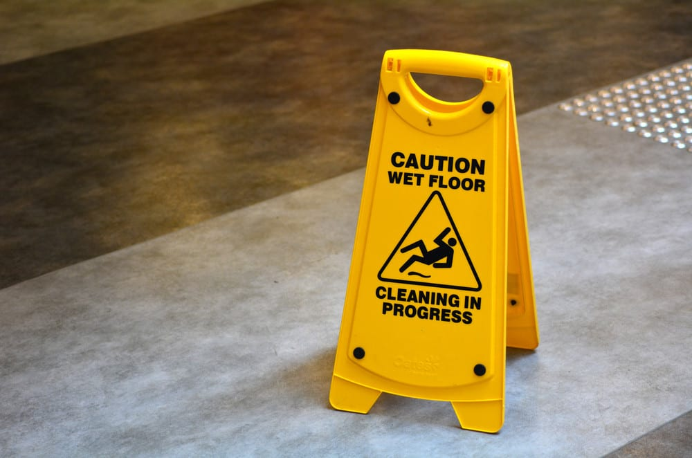 "slippery floor surface warning sign and symbol, reading ""caution wet floor – cleaning in progress"""