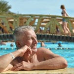 Senior man smiling, leaning over the edge of a pool