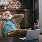 old man sitting in chair listening to headphones, leaning back, smiling