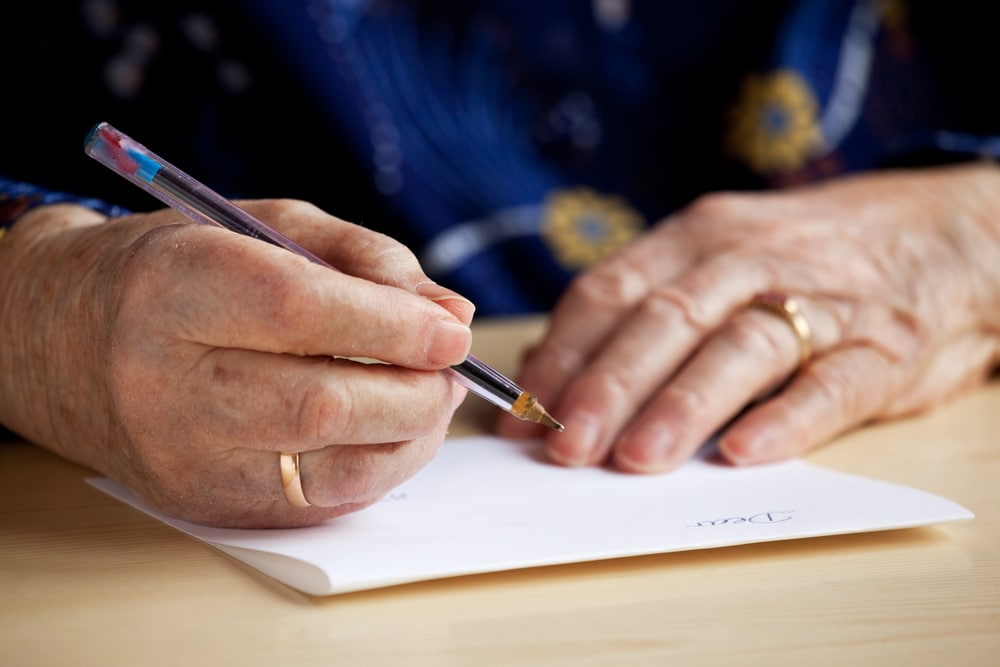 Close-up of senior woman writing letter
