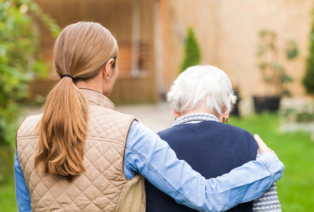 Young-woman-with-arm-around-older-parent-walking-outdoors